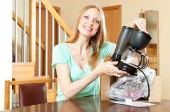 Χαμογελώντας νέα γυναίκα με το νέο ηλεκτρικό κατασκευαστή καφέ behin στο σπίτι Στοκ φωτογραφίες με δικαίωμα ελεύθερης χρήσης