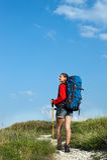 Χαμογελώντας νέα γυναίκα με το σακίδιο πλάτης που εξετάζει το μπλε ουρανό Στοκ Φωτογραφία
