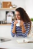 Χαμογελώντας νέα γυναίκα με το φλυτζάνι και το lap-top καφέ μέσα Στοκ Εικόνα
