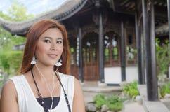 Χαμογελώντας νέα γυναίκα που απολαμβάνει τη μουσική της στοκ φωτογραφίες