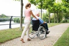 Χαμογελώντας νέα γυναίκα που βοηθά το με ειδικές ανάγκες πατέρα της στην αναπηρική καρέκλα στοκ εικόνες