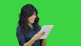 Χαμογελώντας νέα γυναίκα που εργάζεται στον υπολογιστή ταμπλετών σε μια πράσινη οθόνη, κλειδί χρώματος φιλμ μικρού μήκους