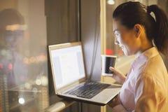 Χαμογελώντας νέα γυναίκα που εργάζεται στο γραφείο στο lap-top της τη νύχτα Στοκ Εικόνες