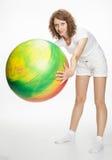 Χαμογελώντας νέα γυναίκα που κάνει τις ασκήσεις με το μεγάλο fitball Στοκ Εικόνα