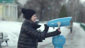 Χαμογελώντας νέα γυναίκα που κοιτάζει μέσω του τηλεσκοπίου στο χειμερινό πάρκο απόθεμα βίντεο