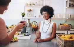 Χαμογελώντας νέα γυναίκα που μιλά σε έναν πελάτη στο φραγμό χυμού Στοκ Φωτογραφία