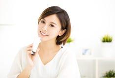 Χαμογελώντας νέα γυναίκα που παρουσιάζει skincare προϊόντα Στοκ Εικόνες