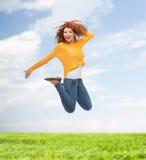 Χαμογελώντας νέα γυναίκα που πηδά στον αέρα Στοκ εικόνα με δικαίωμα ελεύθερης χρήσης