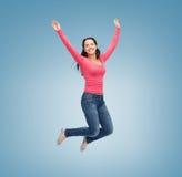 Χαμογελώντας νέα γυναίκα που πηδά στον αέρα Στοκ Φωτογραφίες
