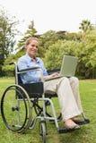 Χαμογελώντας νέα γυναίκα σε μια αναπηρική καρέκλα με ένα lap-top Στοκ φωτογραφία με δικαίωμα ελεύθερης χρήσης