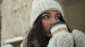 Χαμογελώντας νέα γυναίκα στα άσπρα θερμά ενδύματα με και τον καφέ κατανάλωσης για να πάρει μαζί πέρα από το χιονώδες υπόβαθρο πόλ φιλμ μικρού μήκους