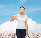 Χαμογελώντας νέα γυναίκα στην κενή άσπρη μπλούζα Στοκ φωτογραφία με δικαίωμα ελεύθερης χρήσης