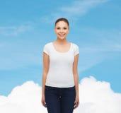 Χαμογελώντας νέα γυναίκα στην κενή άσπρη μπλούζα Στοκ Φωτογραφία
