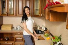 Χαμογελώντας νέα γυναίκα στην κουζίνα με τα λαχανικά στοκ φωτογραφία