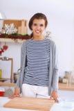 Χαμογελώντας νέα γυναίκα στην κουζίνα, που απομονώνεται επάνω Στοκ εικόνα με δικαίωμα ελεύθερης χρήσης