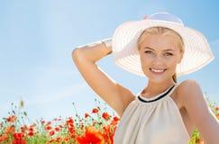 Χαμογελώντας νέα γυναίκα στο καπέλο αχύρου στον τομέα παπαρουνών Στοκ Εικόνα