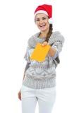 Χαμογελώντας νέα γυναίκα στο πουλόβερ και καπέλο Χριστουγέννων που δίνει την επιστολή Στοκ Εικόνες