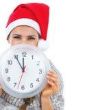 Χαμογελώντας νέα γυναίκα στο πουλόβερ και κρύψιμο καπέλων Χριστουγέννων πίσω από το CL Στοκ Φωτογραφίες