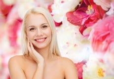 Χαμογελώντας νέα γυναίκα σχετικά με το δέρμα προσώπου της Στοκ φωτογραφίες με δικαίωμα ελεύθερης χρήσης