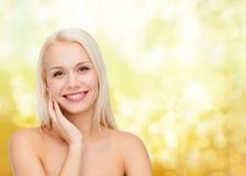 Χαμογελώντας νέα γυναίκα σχετικά με το δέρμα προσώπου της Στοκ Εικόνες