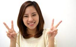 Χαμογελώντας νέα γυναίκα δύο χειρονομία χεριών σημαδιών ειρήνης δάχτυλων Στοκ Εικόνες