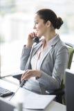 Χαμογελώντας νέα επιχειρηματίας που μιλά στο τηλέφωνο γραμμών εδάφους στην αρχή Στοκ Εικόνες