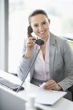 Χαμογελώντας νέα επιχειρηματίας που μιλά στο τηλέφωνο στην αρχή Στοκ Εικόνες