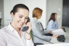 Χαμογελώντας νέα επιχειρηματίας που χρησιμοποιεί το τηλέφωνο γραμμών εδάφους με τους συναδέλφους στο υπόβαθρο στο γραφείο στοκ φωτογραφία με δικαίωμα ελεύθερης χρήσης