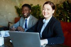 Χαμογελώντας νέα επιχειρηματίας στη συνεδρίαση με το συνάδελφο Στοκ εικόνα με δικαίωμα ελεύθερης χρήσης