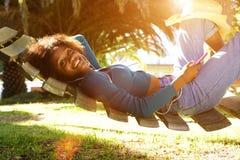 Χαμογελώντας νέα μαύρη γυναίκα που ακούει τη μουσική με το έξυπνο τηλέφωνο Στοκ φωτογραφία με δικαίωμα ελεύθερης χρήσης