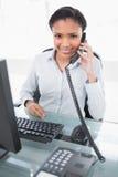 Χαμογελώντας νέα μελαχροινή μαλλιαρή επιχειρηματίας που απαντά στο τηλέφωνο Στοκ φωτογραφία με δικαίωμα ελεύθερης χρήσης