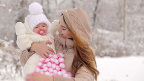 Χαμογελώντας νέα μητέρα με το παιδί το χειμώνα απόθεμα βίντεο
