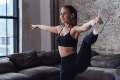 Χαμογελώντας νέα φίλαθλος που κάνει την κάθετη διασπασμένη άσκηση που στέκεται σε ένα πόδι που κρατά το πόδι της στο σπίτι στοκ εικόνα με δικαίωμα ελεύθερης χρήσης