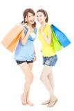 Χαμογελώντας νέες αδελφές που στέκονται και που κρατούν τις τσάντες αγορών Στοκ Εικόνα