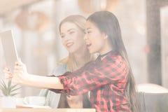 Χαμογελώντας νέες γυναίκες που πίνουν τον καφέ και που χρησιμοποιούν την ψηφιακή ταμπλέτα από κοινού Στοκ Εικόνα