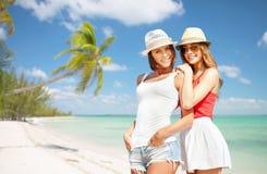 Χαμογελώντας νέες γυναίκες στα καπέλα στην παραλία Στοκ Φωτογραφία