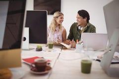Χαμογελώντας νέοι συνάδελφοι που κάθονται μαζί στο δημιουργικό γραφείο Στοκ Φωτογραφία