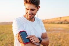 Χαμογελώντας νέος αθλητικός τύπος που χρησιμοποιεί το κενό κινητό τηλέφωνο οθόνης armband Στοκ Εικόνες