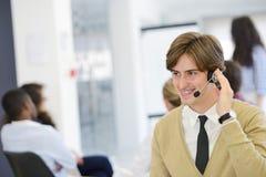 Χαμογελώντας νέος ανώτερος υπάλληλος τηλεφωνικών κέντρων στο γραφείο ξεκινήματος Στοκ Φωτογραφίες
