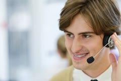 Χαμογελώντας νέος ανώτερος υπάλληλος τηλεφωνικών κέντρων στο γραφείο ξεκινήματος Στοκ φωτογραφία με δικαίωμα ελεύθερης χρήσης