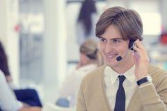 Χαμογελώντας νέος ανώτερος υπάλληλος τηλεφωνικών κέντρων στο γραφείο ξεκινήματος Στοκ εικόνες με δικαίωμα ελεύθερης χρήσης