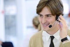 Χαμογελώντας νέος ανώτερος υπάλληλος τηλεφωνικών κέντρων στο γραφείο ξεκινήματος Στοκ Φωτογραφία