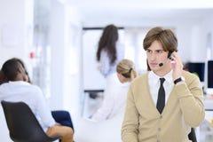 Χαμογελώντας νέος ανώτερος υπάλληλος τηλεφωνικών κέντρων στο γραφείο ξεκινήματος Στοκ Εικόνες