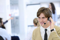 Χαμογελώντας νέος ανώτερος υπάλληλος τηλεφωνικών κέντρων στο γραφείο ξεκινήματος Στοκ εικόνα με δικαίωμα ελεύθερης χρήσης