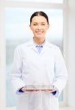 Χαμογελώντας νέος γιατρός με το PC ταμπλετών στο γραφείο Στοκ Εικόνα