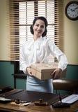 Χαμογελώντας νέος γραμματέας που κρατά μια συσκευασία ταχυδρομείου στοκ εικόνες