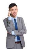 Χαμογελώντας νέος επιχειρηματίας που απαντά στο τηλέφωνο Στοκ Εικόνες