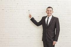 Χαμογελώντας νέος επιχειρηματίας που εξετάζει τη κάμερα δείχνοντας σε ομο Στοκ φωτογραφία με δικαίωμα ελεύθερης χρήσης