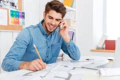 Χαμογελώντας νέος επιχειρηματίας που μιλά στο κινητό τηλέφωνο και την παραγωγή των σημειώσεων Στοκ Εικόνες