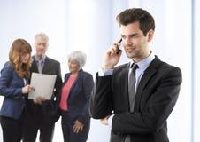 Χαμογελώντας νέος επιχειρηματίας που μιλά στο κινητό τηλέφωνο Στοκ Εικόνα